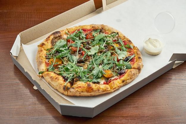 Foto per la consegna della pizza. pizza vegetariana con olive, formaggio fuso, rucola, funghi, pomodorini