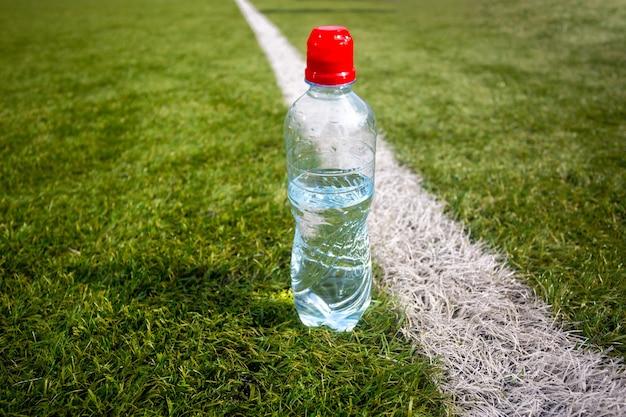 Foto di una bottiglia d'acqua di plastica sull'erba verde del campo di calcio