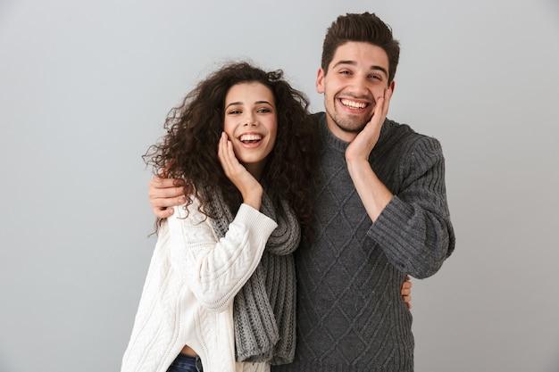 Foto di felice coppia uomo e donna che ride e tocca il viso, isolato sopra il muro grigio