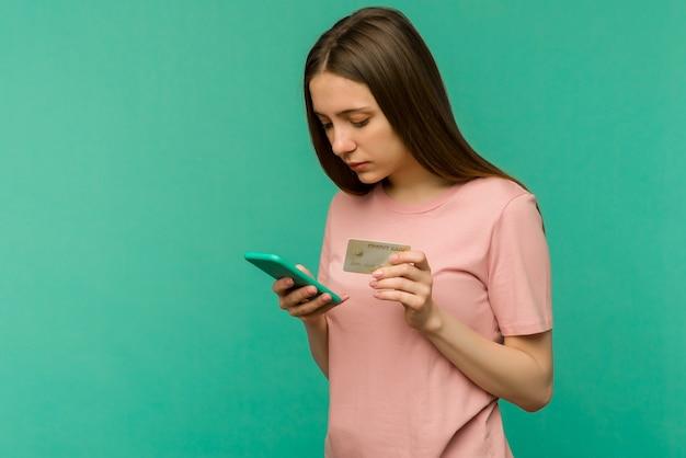 Foto di felice felice urlando giovane donna in posa isolato su sfondo blu muro utilizzando il telefono cellulare in possesso di carta di credito.