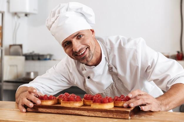 Foto del capo maschio soddisfatto in zolla bianca uniforme della tenuta con le torte