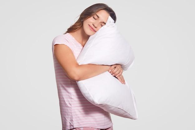 Foto di felice giovane donna europea di buon umore, abbraccia morbido cuscino, vestita in pigiama, pone contro il muro bianco. adolescente rilassato dorme al coperto. concetto di riposo e stile di vita