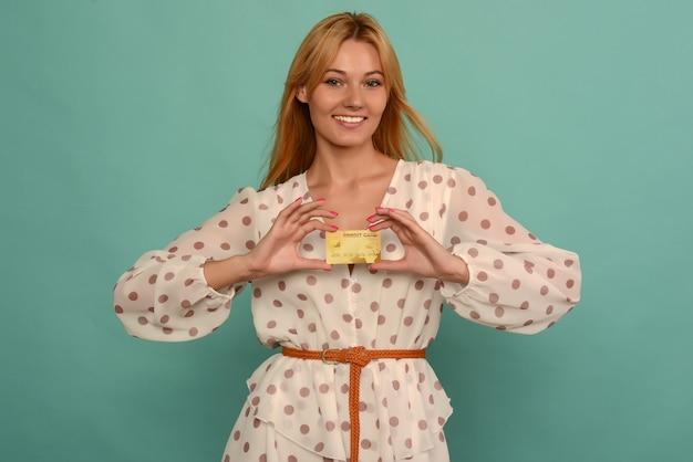 Foto di felice giovane donna in posa isolato su sfondo blu muro in possesso di carta di debito o di credito.