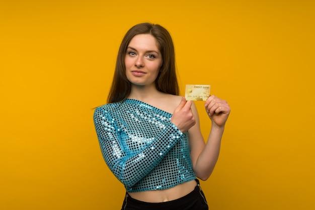 Foto di felice giovane donna in posa isolato su sfondo giallo muro tenendo la carta di debito o di credito.