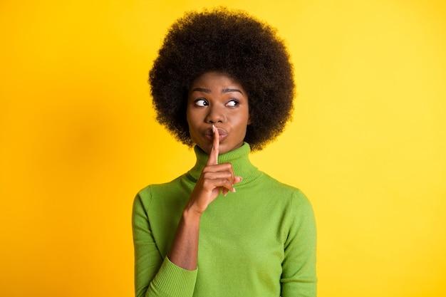 Ritratto fotografico di una ragazza afroamericana che tocca le labbra con il dito che dice di zittire isolato su uno sfondo di colore giallo brillante