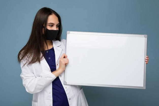 Foto ritratto di attraente bruna giovane donna che indossa camice medico bianco e maschera nera che tiene bordo bianco