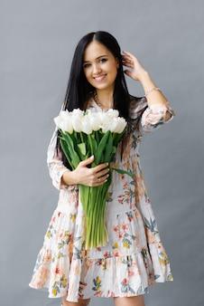 Ritratto fotografico di una ragazza bruna che tiene tra le mani un mazzo di tulipani bianchi, fiori isolati su uno sfondo grigio.