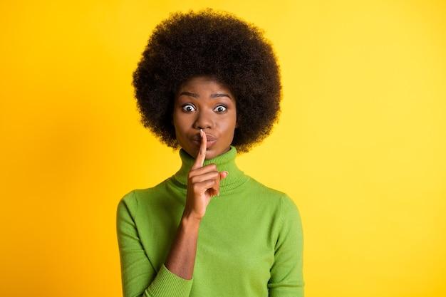 Ritratto fotografico di una donna bruna che tocca le labbra chiedendo silenzio isolato su uno sfondo di colore giallo vivido