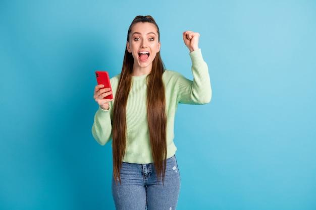 Foto ritratto di donna allegra che tiene il telefono in una mano pugno in alto isolato su sfondo colorato blu pastello