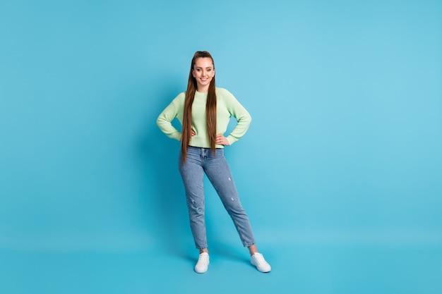 Foto ritratto di ragazza sicura di sé con le mani sulla vita isolato su sfondo colorato blu pastello