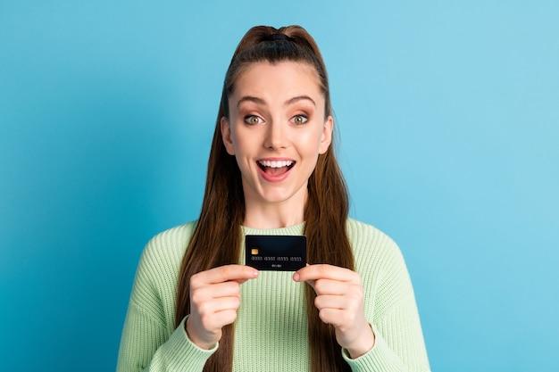 Foto ritratto di ragazza eccitata in possesso di carta di credito con due mani bocca aperta isolata su sfondo colorato blu pastello