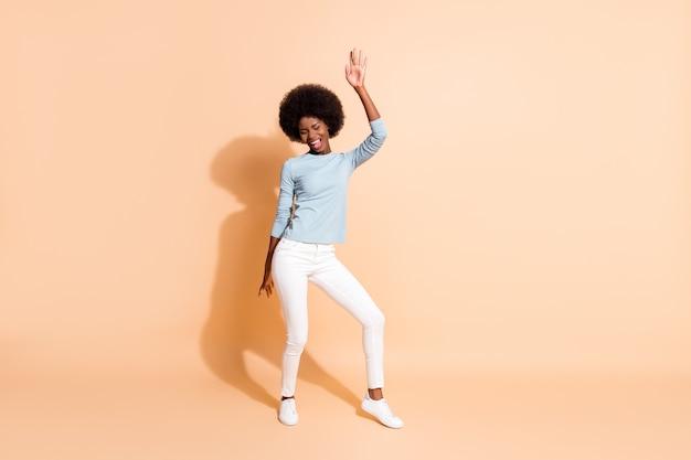 Foto ritratto vista completa del corpo della donna afroamericana che balla isolato su sfondo colorato beige pastello