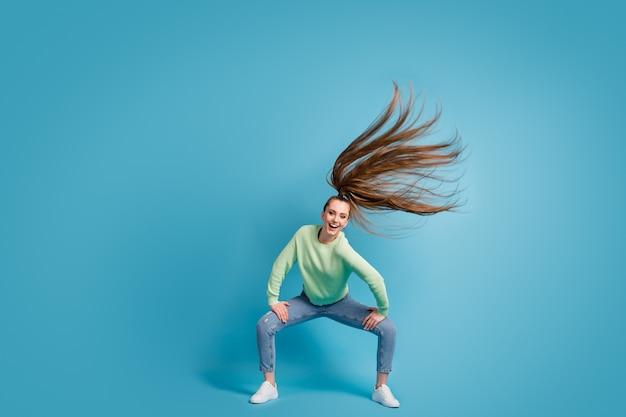 Ritratto fotografico di una ragazza che balla twerk con i capelli al vento isolati su sfondo colorato blu pastello