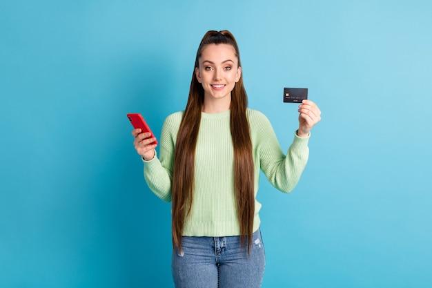 Foto ritratto di ragazza che tiene la carta di plastica del telefono nelle mani isolate su sfondo colorato blu pastello