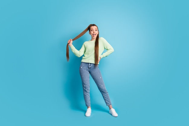 Foto ritratto di ragazza che mostra la lingua che tiene i capelli isolati su sfondo colorato blu pastello