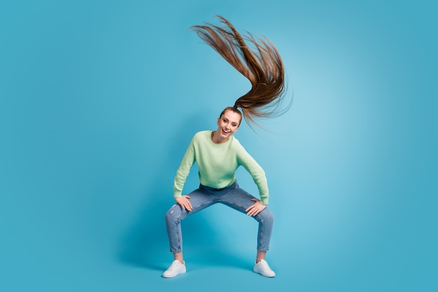 Foto ritratto di una ragazza che ride twerking agitando i capelli isolati su sfondo colorato blu pastello