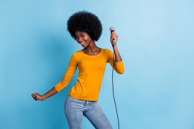 Foto ritratto di una bella ragazza dalla pelle nera che tiene il microfono sorridente che balla in discoteca isolata su uno sfondo di colore blu vibrante