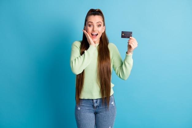 Ritratto fotografico di una donna urlante che tiene in mano una carta di plastica con le dita che toccano il viso con la mano isolata su uno sfondo di colore blu pastello