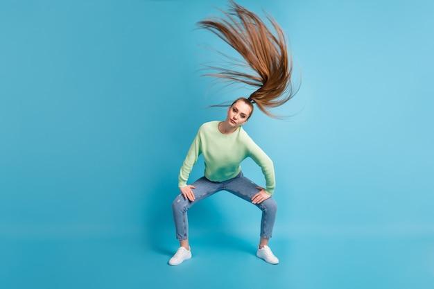 Foto ritratto di ragazza seria twerking agitando i capelli isolati su sfondo colorato blu pastello