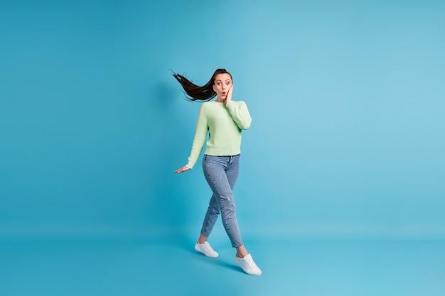 Foto ritratto di donna scioccata che cammina toccando la guancia del viso con una mano isolata su sfondo colorato blu pastello