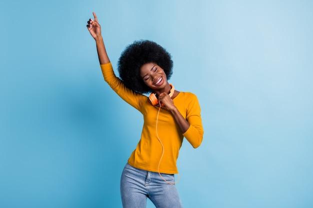 Ritratto fotografico di una ragazza sorridente dalla pelle nera che indossa gli auricolari che balla puntando il dito verso l'alto ridendo isolato su uno sfondo di colore blu brillante