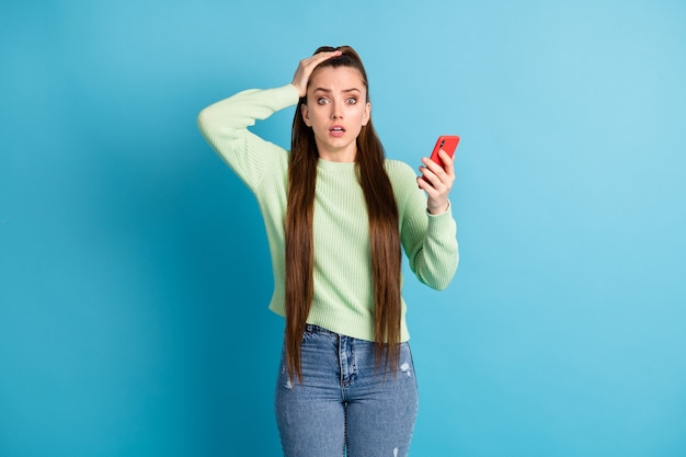 Foto ritratto di ragazza infelice che tiene il telefono con la testa con una mano isolata su sfondo colorato blu pastello