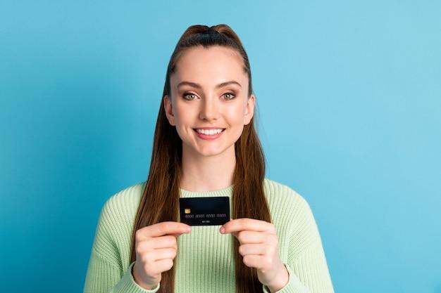 Foto ritratto di donna in possesso di carta di credito con due dita delle mani isolate su sfondo colorato blu pastello