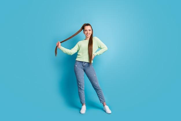 Ritratto fotografico di donna che tiene i capelli isolati su sfondo colorato blu pastello