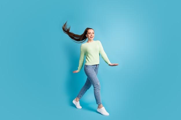 Foto ritratto di donna che cammina sorridente isolato su sfondo colorato blu pastello