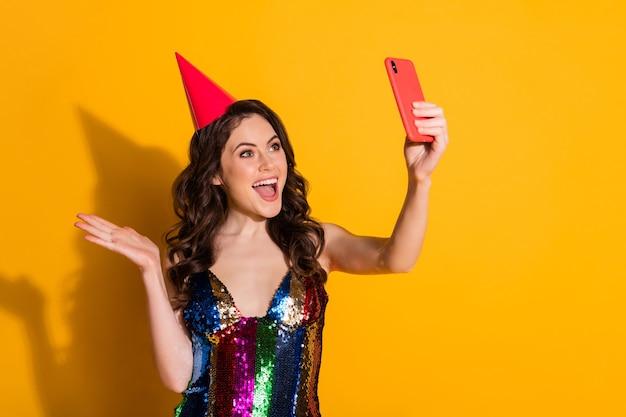 Foto di positivo allegro stupito ragazza blogger prendere selfie smartphone festa di compleanno videochiamata indossare gonna copricapo cono rosso isolato su sfondo di colore giallo