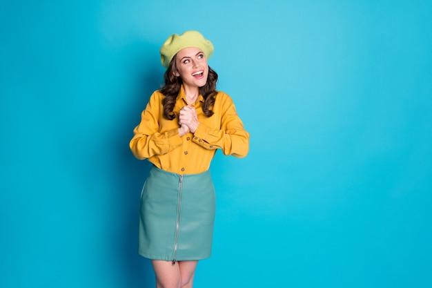 Foto di una ragazza allegra positiva impressionata desiderio desiderio presente annunci regalo aspetto copyspace impressionato indossare copricapo isolato su sfondo blu