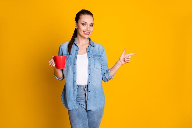 La foto del promotore positivo della ragazza allegra tiene la tazza con il dito indice del punto del caffè espresso del latte copyspace indica che la promozione degli annunci indossa l'abito alla moda alla moda isolato sfondo luminoso brillante di colore