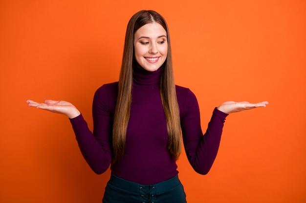 Foto di una ragazza allegra positiva promotrice tenere la mano presente vendita oggetto sconto offerta confronto misurazione indossare abito viola isolato su un colore brillante sfondo