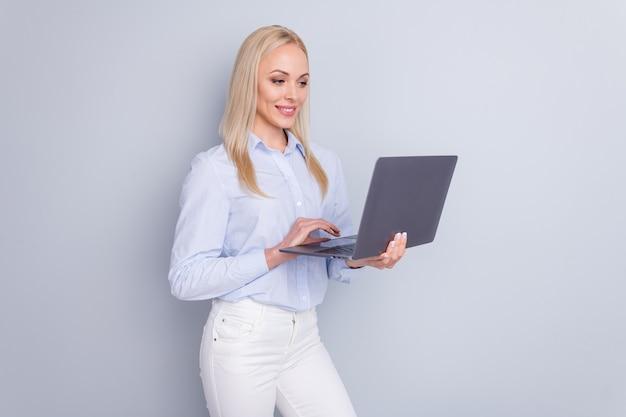 La foto della ragazza allegra positiva usa il computer portatile su fondo grigio