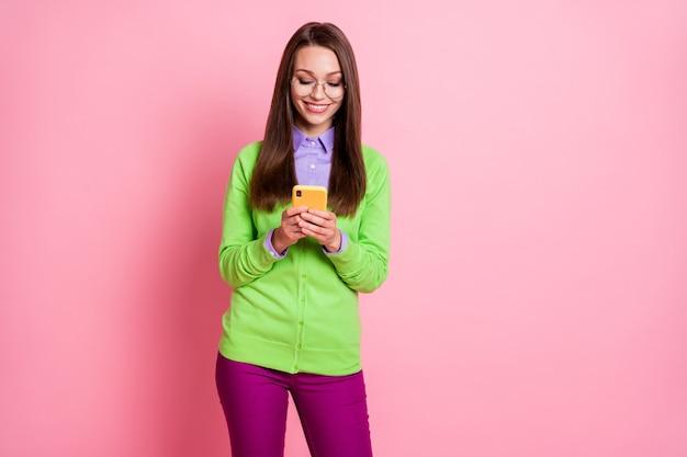 Foto di una ragazza allegra positiva che usa uno smartphone indossa pantaloni viola verdi pantaloni isolati su uno sfondo di colore pastello