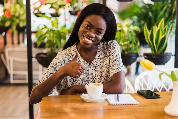 La foto della femmina di razza mista dalla pelle scura positiva gode di un buon riposo al bar, beve bevande calde, ha un ampio sorriso, felice di discutere di qualcosa di divertente con gli amici. persone, tempo libero e concetto di mangiare