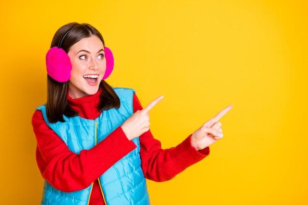 Foto positivo eccitato ragazza promotore guardare incredibili annunci promo vendite godere punto dito indice consigliare suggerire selezionare indossare rosa maglione blu isolato brillante brillante colore sfondo