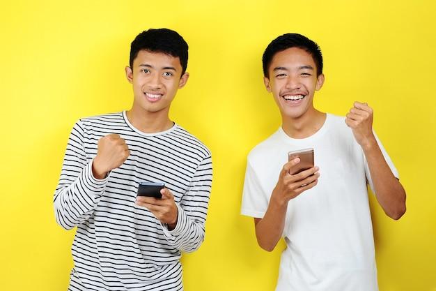 Foto di due uomini asiatici entusiasti positivi che sorridono usando i telefoni cellulari isolati su sfondo giallo