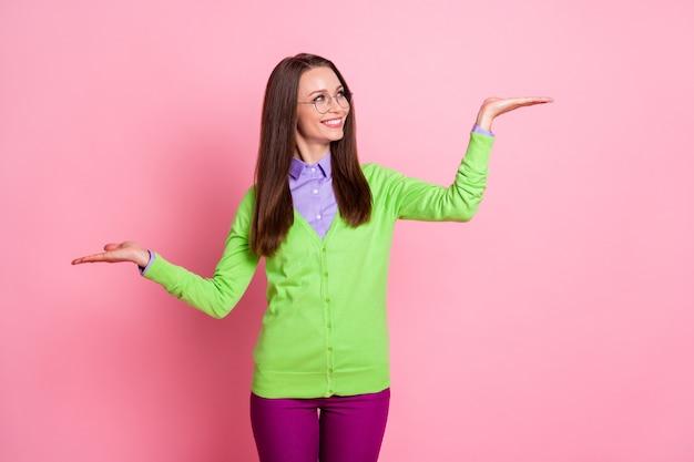 Foto di una ragazza positiva che tiene la mano copyspace indossa una camicia verde pantaloni viola isolato sfondo di colore rosa