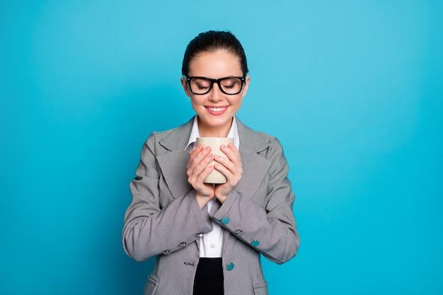 Foto di una ragazza positiva che tiene in mano una tazza di odore di bevanda indossa un blazer grigio isolato su uno sfondo di colore blu