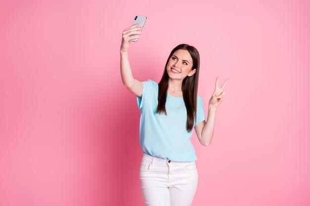 La foto della ragazza positiva fa il segno di v usa lo smartphone prende selfie indossa pantaloni blu bianchi isolati sfondo color pastello