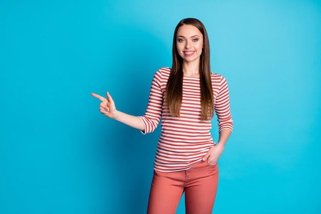 Foto di una ragazza positiva promotore punto dito indice copyspace presente pubblicità promozione dimostrare le vendite indossare un bell'aspetto vestiti isolati su sfondo di colore blu