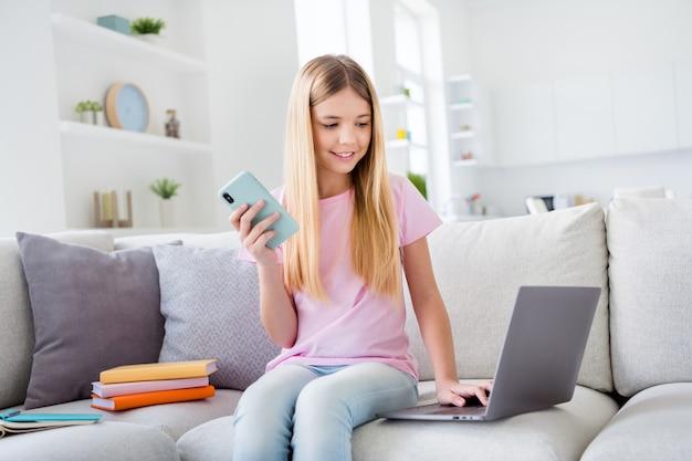 La foto di una ragazza positiva si siede sul divano ha l'istruzione a casa usa il laptop controlla la notifica dei social media tieni lo smartphone comunica gli amici in casa al chiuso