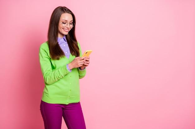 Foto di una ragazza positiva che usa lo smartphone indossa pantaloni viola verdi e pantaloni isolati su uno sfondo di colore pastello