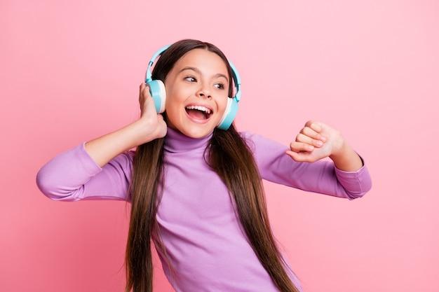Foto di una bambina hipster positiva che ascolta la playlist su un auricolare wireless balla isolata su uno sfondo di colore pastello
