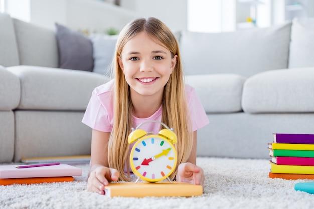Foto di una ragazzina positiva che giace sul pavimento dimostra un orologio giallo aiuta a essere puntuale nello studio a distanza da non perdere online insegnante tutor lezione sdraiato sul pavimento tappeto in casa al chiuso