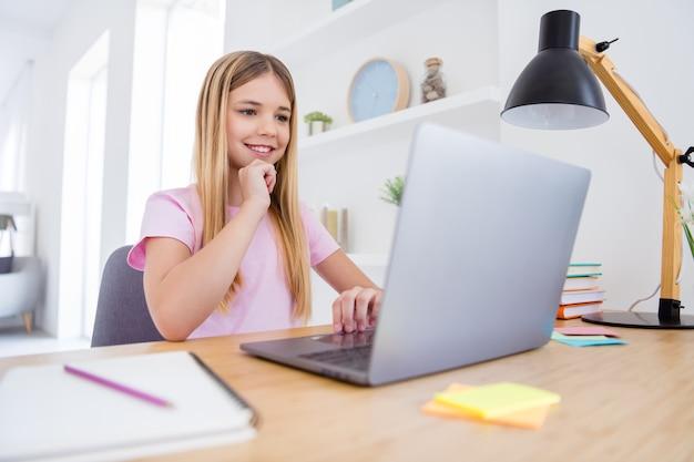 Foto di una ragazza positiva che si siede al tavolo, studia, usa il computer a distanza, leggi, guarda, video, webinar, tocca la mano, il mento in casa, al chiuso