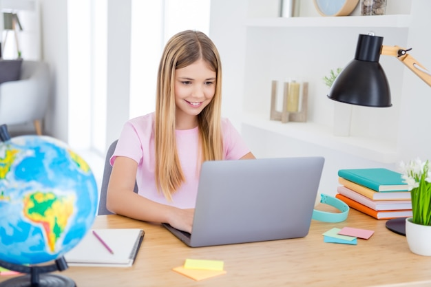 Foto di una ragazzina positiva che si siede alla scrivania studiando lo smartphone per uso remoto ha una lezione di comunicazione online con un tutor in casa al chiuso