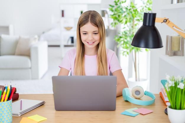 Foto di una ragazzina positiva che studia a distanza il tavolo della scrivania usa il laptop ha una lezione di comunicazione online con il tutor che scrive un rapporto in casa al chiuso