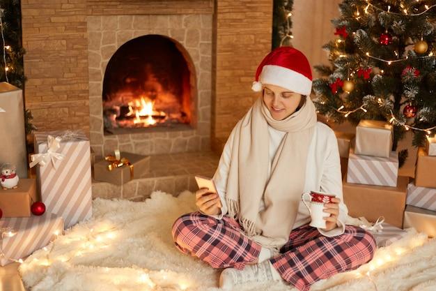 Foto della signora positiva che si siede con il cellulare e che tiene la tazza della bevanda in casa all'interno